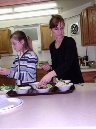 Thea Julien makes a salad with a Challenge team member during an event for Challenge parents