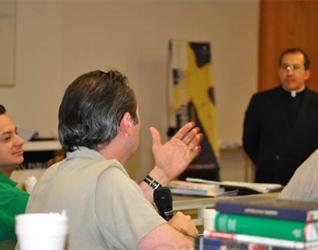 Uno de los señores hace una pregunta al P. Juan Antonio Torres sobre la evangelización en la empresa.