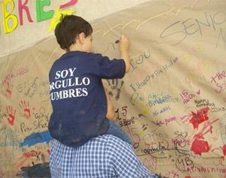 Un alumno del colegio escribe en el muro del recuerdo.