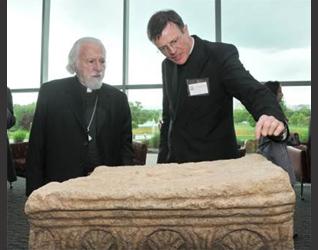 El P. Eamon explica los detalles en una réplica de la piedra esculpida de Magdala a Su Eminencia Isaiah, Metropolita de los ortodoxos griegos de Denver.
