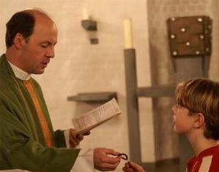 El P. Klaus entrega la corona del rosario a un niño durante las incorporaciones al ECYD en el noviciado de Bad Münstereifel.