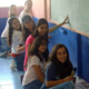 Grupo de chicas pitando una escuela de escasos recursos.