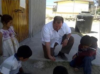 El P. Isidro juega canicas con un grupo de niños durante unas misiones.