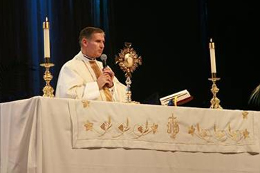 El P. Juan Rivas, L.C. ante el Santísimo expuesto al final de la santa misa.