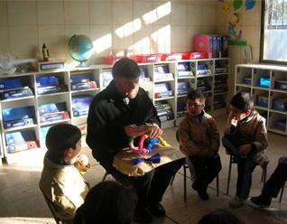 El P. Jaime Ortiz de Lazcano, de la parroquia Emanuel, recibe un regalo de los niños del Colegio Mano Amiga de Recoleta, el primero de los tres colegios para niños de escasos recursos en Chile.