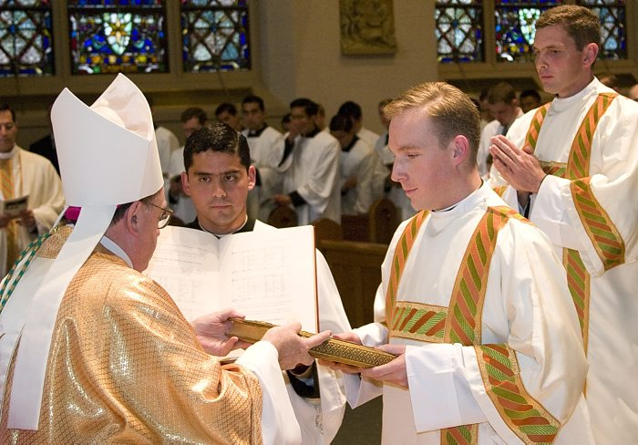 Fr. Michael receives the Book of the Gospels from Bishop Dennis Sullivan, auxiliary bishop of New York, during his ordination to the diaconate on June 14, 2009.