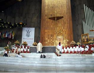 Mons. Pedro Pablo Elizondo, L.C., durante la letanía de los santos con los dos diáconos (postrados ante el altar) que recibieron la ordenación sacerdotal en la misa de la peregrinación de la Prelatura de Cancún-Chetumal.